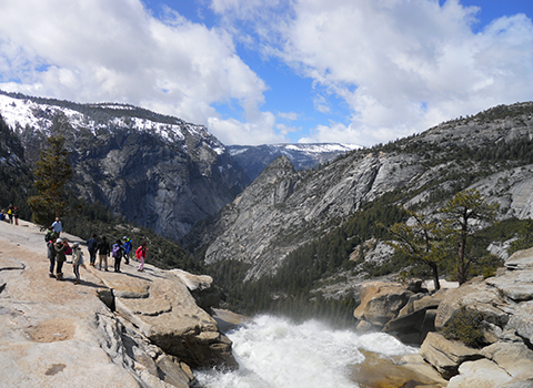 Yosemite National Park with waterfall in foreground and mountains in background