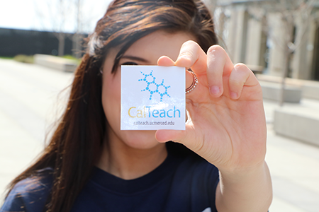 Image of student holding sticker with CalTeach logo.